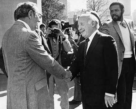Joseph E. Cole (right) shakes hands with Herb Kamm, 1980