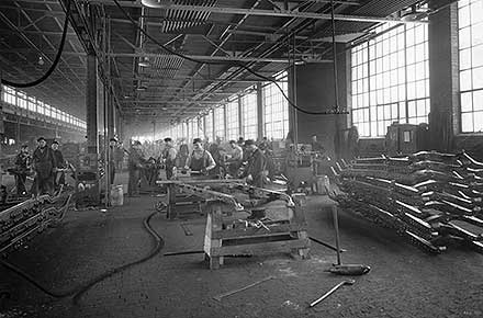 Laborers assemble steel frames on factory floor